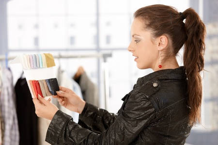 Young attractive fashion designer working in bright office, looking at colour scale. photo