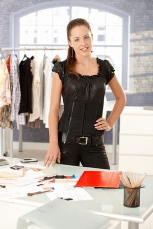 Young attractive fashion designer standing by desk in office, smiling. photo
