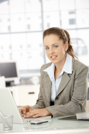 Attractive young businesswoman working on laptop in bright office. Stock Photo - 8251298