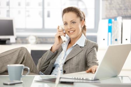 businesswoman suit: Atractiva empresaria sentado en el escritorio, hablando por tel�fono, con el port�til, sonriendo.  Foto de archivo