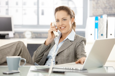 Attractive businesswoman sitting at desk, talking on phone, having laptop, smiling. photo