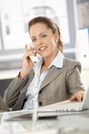 Attractive businesswoman sitting at desk, talking on phone, having laptop, smiling. Stock Photo - 8251377