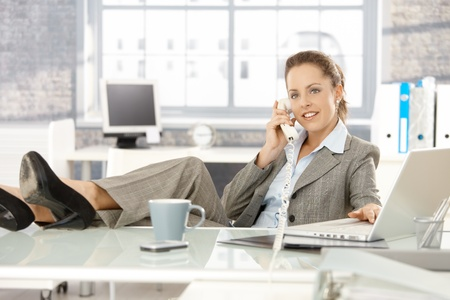 Young attractive businesswoman sitting at desk, legs on top of desk, talking on phone, smiling. photo