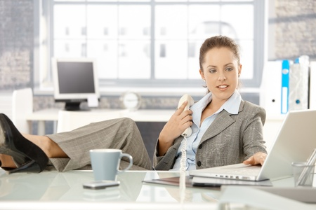 Young attractive businesswoman sitting at desk in bright office, holding away phone while checking information on laptop, resting legs on top of desk. photo
