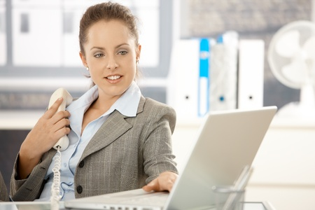 Young attractive businesswoman sitting at desk in bright office, holding away phone while checking information on laptop, smiling. Stock Photo - 8251299