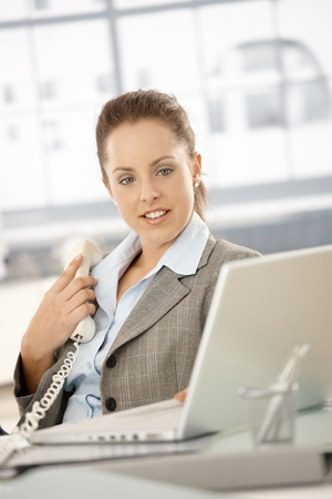 Young attractive businesswoman sitting by desk in bright office, holding away phone while checking information on laptop, smiling. Stock Photo - 8251291