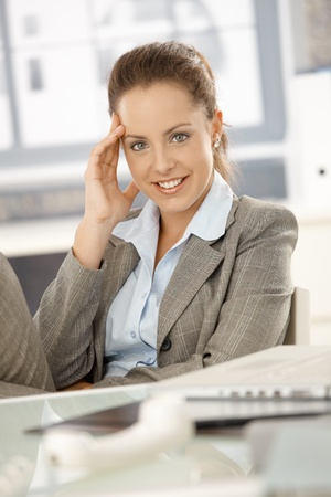 Young attractive businesswoman sitting by desk in bright office, taking a break, smiling. Stock Photo - 8251379