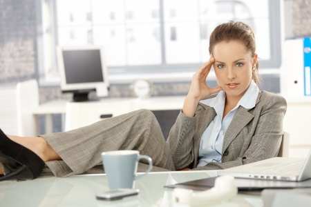 Young attractive businesswoman sitting at desk in office, looking tired, resting legs on desk. photo