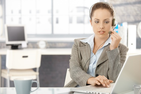 dispatcher: Young attractive dispatcher working in bright office, using headphones and laptop. Stock Photo