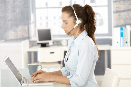 chat room: Young dispatcher working in bright office, using laptop and headphones, typing.
