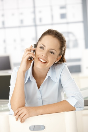 Young attractive female sitting on conversed chair, talking on mobile phone, smiling. Stock Photo - 8250999