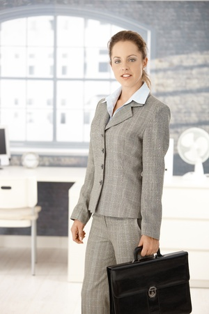 Attractive young businesswoman leaving office after work, holding briefcase. Stock Photo - 8251383