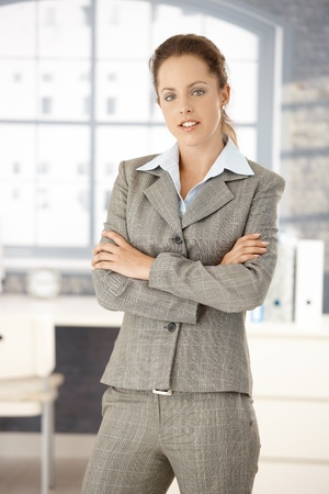 Young attractive woman standing in office front of window, arms crossed. Stock Photo - 8251385