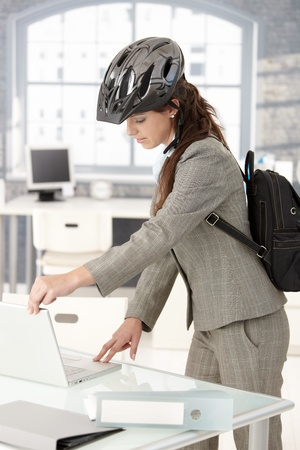 Young attractive businesswoman leaving office by bike, shutting down her laptop, wearing helmet and backpack. photo