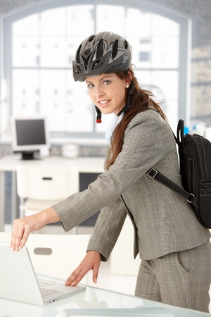 Young attractive businesswoman leaving office by bike, shutting down her laptop, wearing helmet and backpack. Stock Photo - 8251382