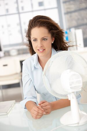 Young attractive woman sitting in office front of fan, feeling hot, cooling herself. photo