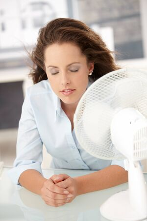 Young attractive woman sitting in office front of fan, feeling hot, cooling herself, eyes closed. photo