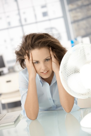 Young attractive woman sitting in office front of fan, feeling hot, cooling herself. Stock Photo - 8250960