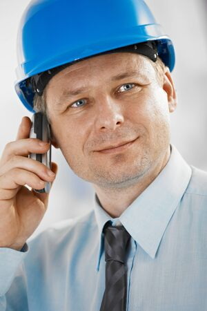 Closeup portrait of architect wearing hardhat, talking on mobile, looking at camera. photo