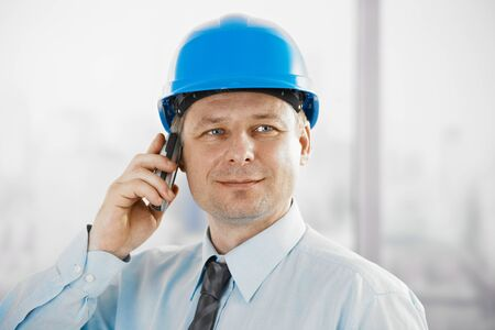 Portrait of architect talking on mobile, looking at camera, smiling. photo