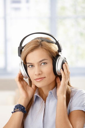 Attractive girl listening music through headphones, front of window. Stock Photo - 8398071