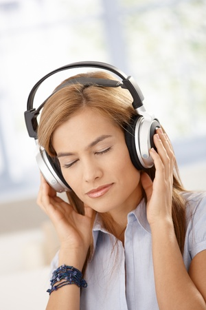 Young woman listening music through headphones, eyes closed. Stock Photo - 8398067