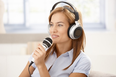 Attractive young woman singing with microphone, wearing headphones, smiling. Stock Photo - 8398053