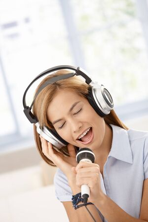 Attractive girl singing eyes closed with joy, smiling. Stock Photo - 8398061