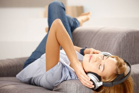 listening back: Young attractive girl enjoying music through headphones, laying on sofa.