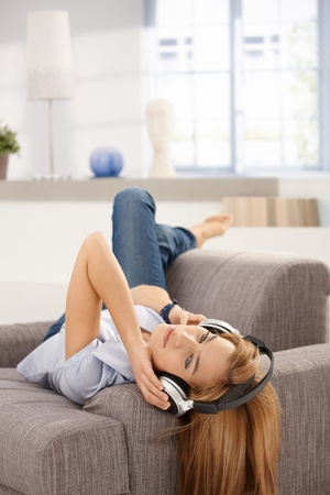 Attractive female laying on sofa, listening music through headphones. photo