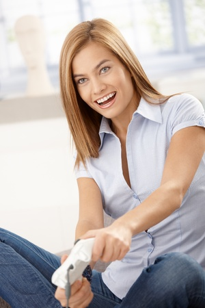 Young attractive female playing video game at home, smiling. Stock Photo - 8398088