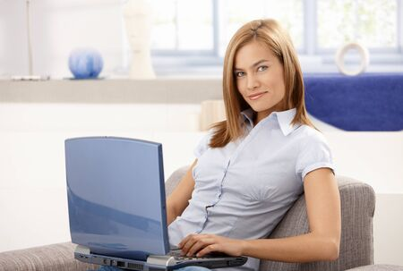 Young attractive woman using laptop at home, sitting on sofa, smiling. Stock Photo - 8398077