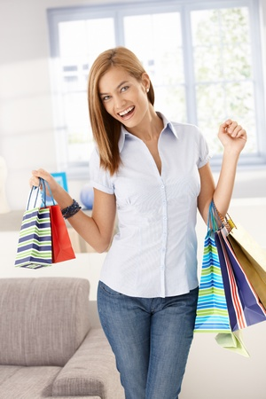 Happy woman standing in living room with shopping bags in hands. photo