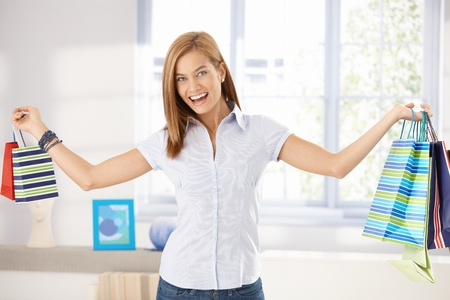 outspreading: Happy woman standing arms wide open, holding shopping bags. Stock Photo
