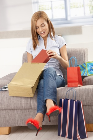 Happy woman opening shopping bags, sitting on sofa, smiling. photo