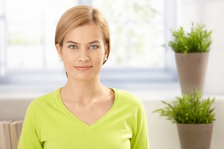 Portrait of attractive young female with plants in vivid green, smiling. photo