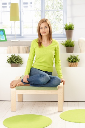 Young attractive girl sitting front of window, plants around, wearing vivid green pullover, smiling. Stock Photo - 8398065
