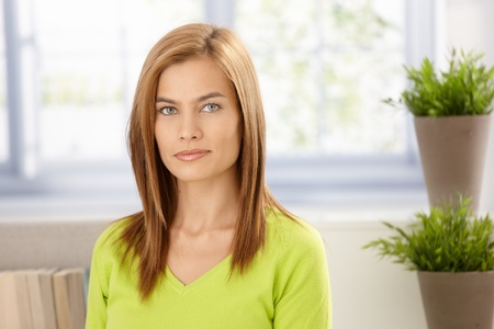Portrait of attractive young woman wearing vivid green pullover smiling front of window. photo