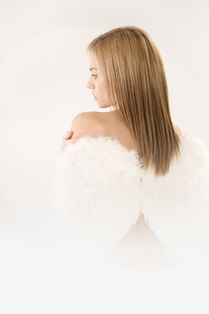 Attractive young girl wearing angel wings, viewed from back. photo