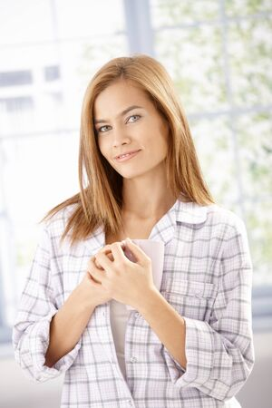 Attractive young woman drinking tea in pyjama in the morning, smiling. photo