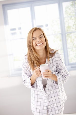 Young attractive female laughing happily, drinking tea in pyjama. Stock Photo - 8398042