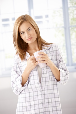 Attractive young girl in pyjama, drinking tea, smiling. photo