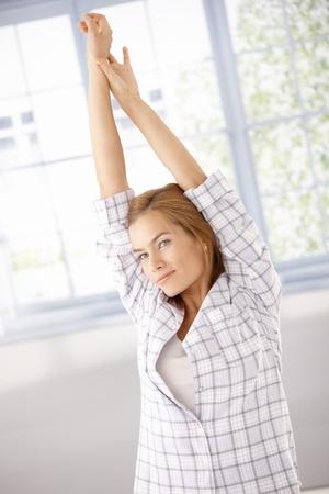 levantandose: Mujer atractiva joven levantarse, que se extiende por la ma�ana en pijama.