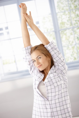 Young attractive woman getting up, stretching in the morning in pyjama. photo