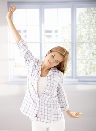 Attractive young girl stretching in the morning at home in pyjama. photo