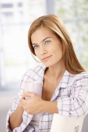 Morning portrait of attractive woman in pyjama, drinking tea. photo
