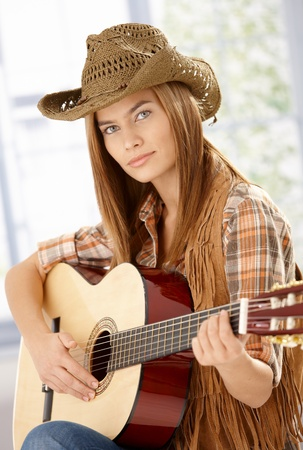 Attractive young female guitar player practicing, wearing western hat. photo