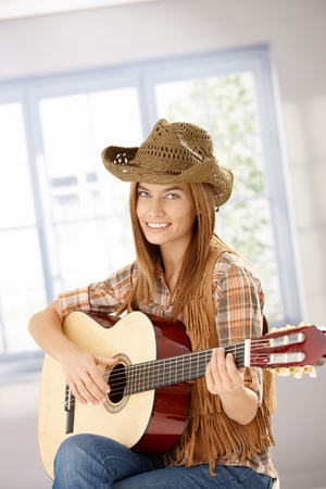 Attractive young girl playing guitar, smiling, wearing western hat. photo