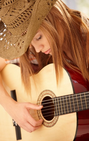 girl playing guitar: Young woman playing guitar with expression in western hat.