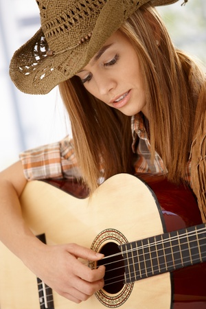 girl playing guitar: Attractive young woman playing guitar with joy, wearing western hat.